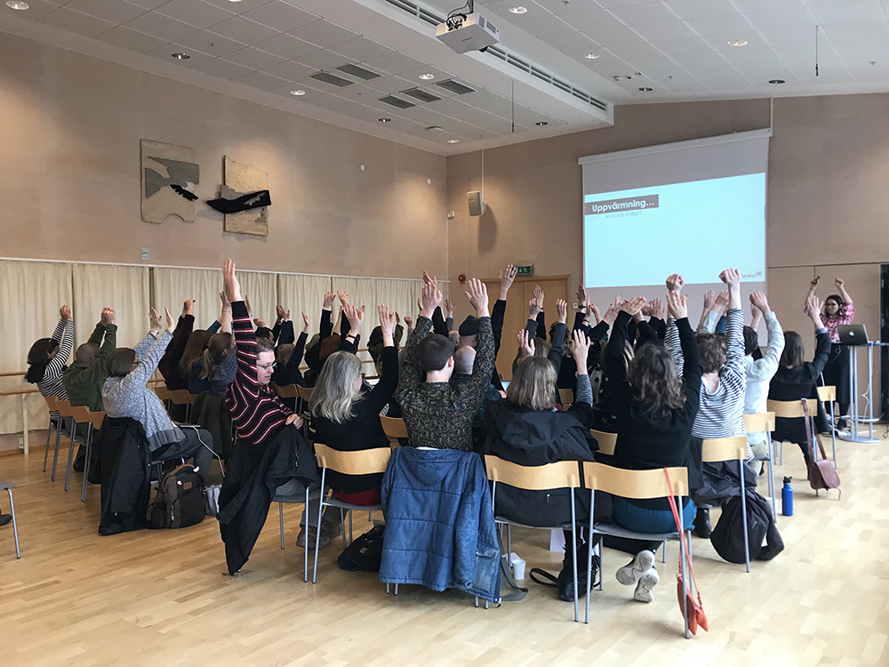 Foto på publik som sträcker upp händerna.