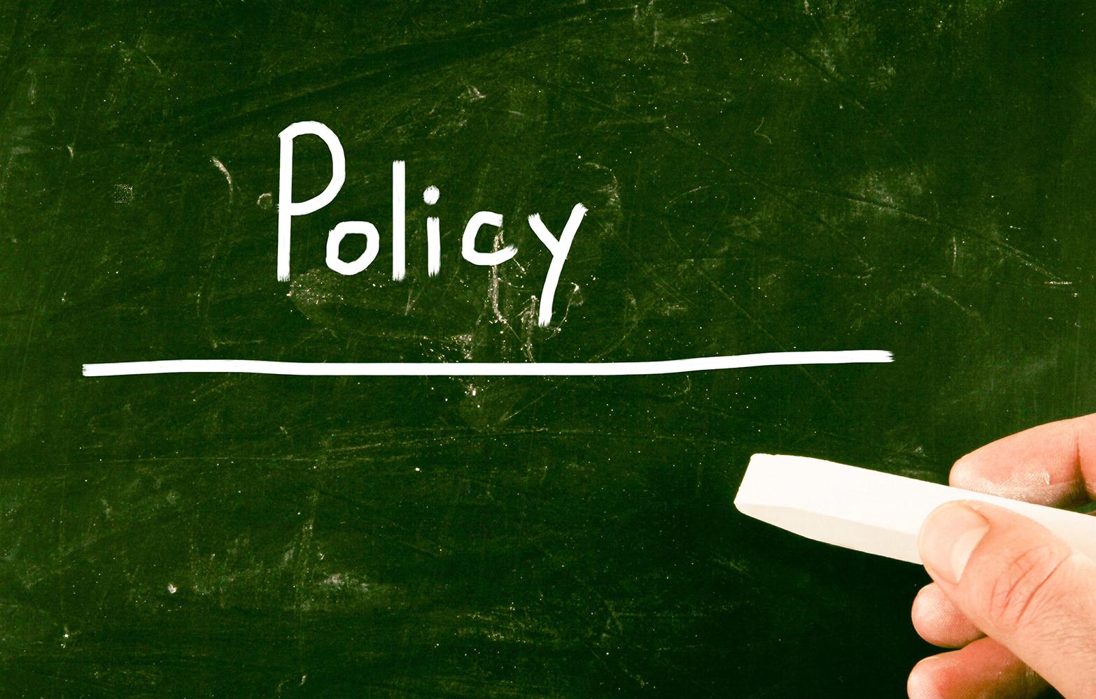 Bild med ordet policyn skrivet med krita på grön skrivtavla
