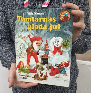 Daniel visar upp boken Tomtarnas glada jul skriven av Vilhelm Hansen