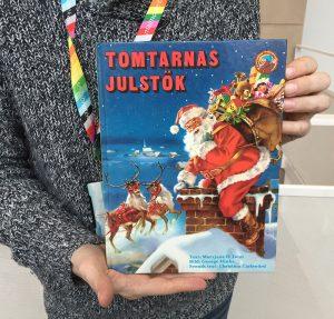Daniel Björklund håller i julboken Tomtarnas julstök av Maryjane H Tonn med illustrationer av George Hinke