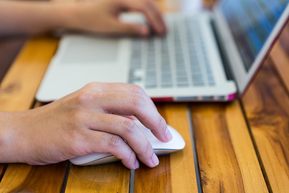 Närbild på en människas händer som arbetar med en Laptop.
